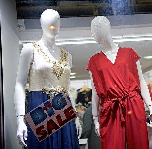 Манекены в витрине магазина с объявлениями о распродаже