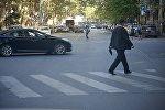Люди переходят дорогу по зебре на регулируемом перекрестке со светофором