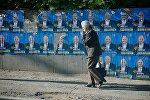 Женщина идет по одной из тбилисских улиц мимо предвыборных плакатов