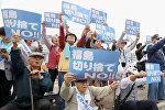 Истцы, которые подали в суд на TEPCO и японское правительство, демонстрируют плакаты перед окружным судом Фукусимы в Фукусиме, Япония