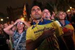 Жители Барселоны слушают речь Карлеса Пучдемона во время заседания регионального парламента Каталонии