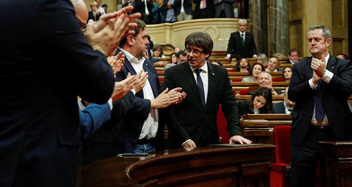 Депутаты регионального парламента Каталонии аплодируют президенту Карлесу Пучдемону после его выступления