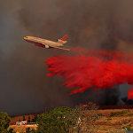 Пожарный самолет DC-10 сбрасывает тонны воды на горящий лес в американском штате Калифорния