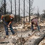 Количество людей, пропавших без вести после начала лесных пожаров в Калифорнии, исчисляется десятками, а число погибших, по официальным данным, достигло 11 человек. На снимке - пожарные и спасатели ищут выживших на развалинах одного из домов