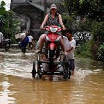 Во Вьетнаме произошло сильное наводнение. На фото - местные жители помогают друг другу переправиться через затопленную дорогу в Ханое