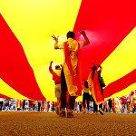 Люди несут огромный флаг Каталонии во время Национального дня Испании в Барселоне