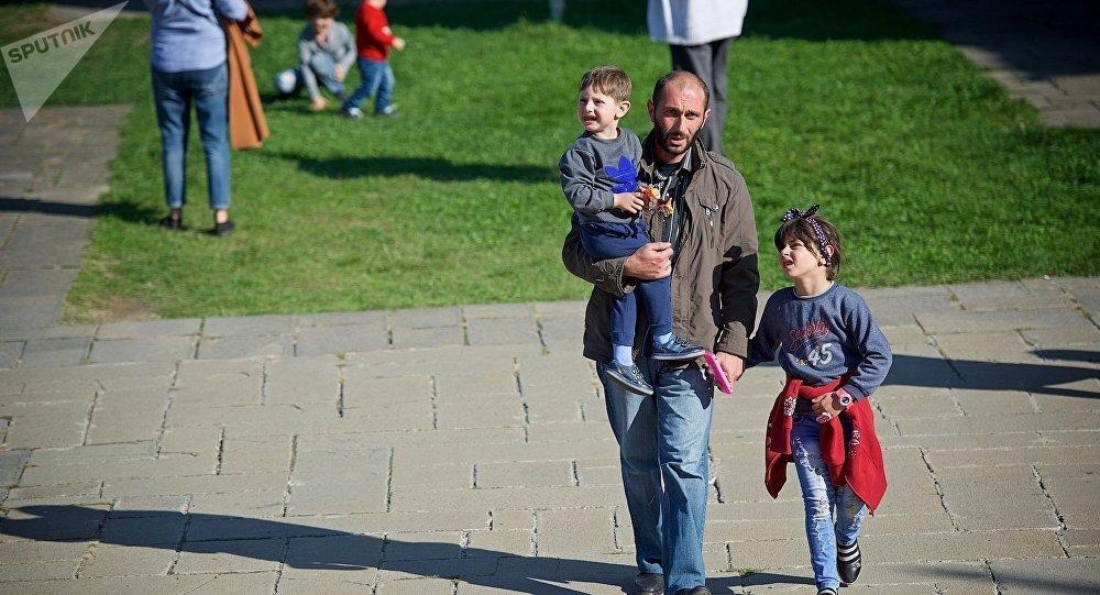 Мужчина идет с детьми по территории храма Светицховели