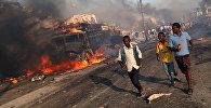 Люди бегут от места взрыва на улице КМ4 в Могадишо, Сомали