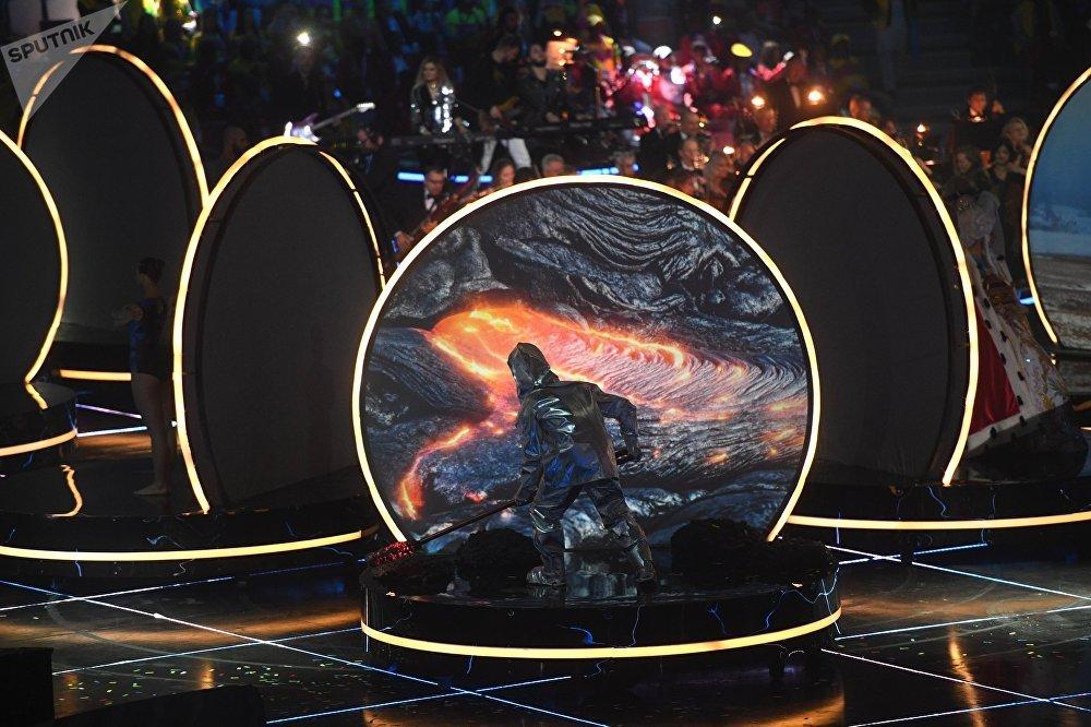 Танцоры, расположившиеся под сценой выполняли различные движения на круглых подмостках в виде открытых ракушек, а на верхнюю часть проецировалась тень с установленных на их костюмах датчиках. Такое оформление соответствовало общему сценарию шоу, посвященному высоким технологиям