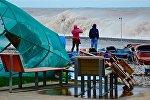 Туристы фотографируют Черное море во время шторма на пляже Батуми