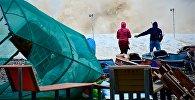 Туристы на берегу Черного моря во время шторма