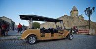 Прогулочный электромобиль на фоне храма Светицховели в городе Мцхета