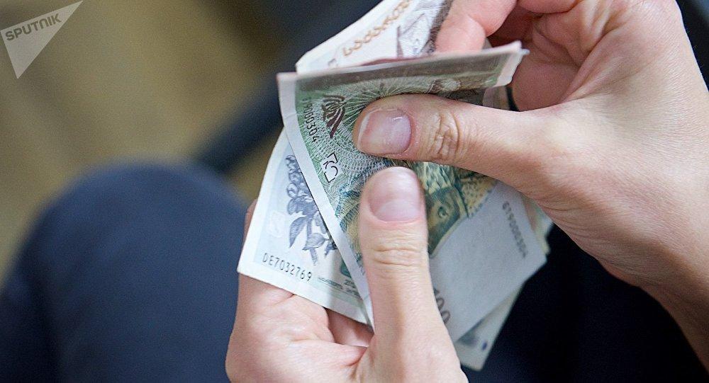 Человек пересчитывает купюры грузинской валюты лари различного номинала