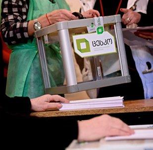 Сотрудники избирательной администрации выносят с участка переносную урну для голосования