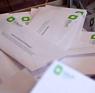 Избирательные бюллетени в урне для голосования во время выборов