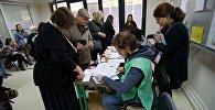 Избиратели проходят регистрацию перед голосованием на избирательном участке