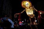 Прохожие смотрят на громадную светящуюся фигуру скелета во время фестиваля фонарей на празднике Хэллоуин в Ливерпуле, Великобритания