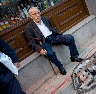 ხანდაზმული მამაკაცი ისვენებს ძაღლის სკულპტურის გვერდზე აღმაშენებლის გამზირზე