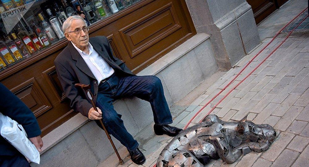 ხანდაზმული მამაკაცი ისვენებს აღმასენებლის გამზირზე ძაღლის სკულპრტურის გვერდზე