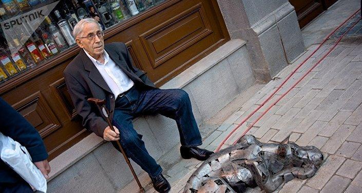 Пожилой мужчина отдыхает, сидя рядом со скульптурой собаки на проспекте Агмашенебели