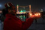Житель Пакистана держит в руках горящие свечи