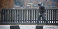 Студент с рюкзаком переходит мост в центре грузинской столицы