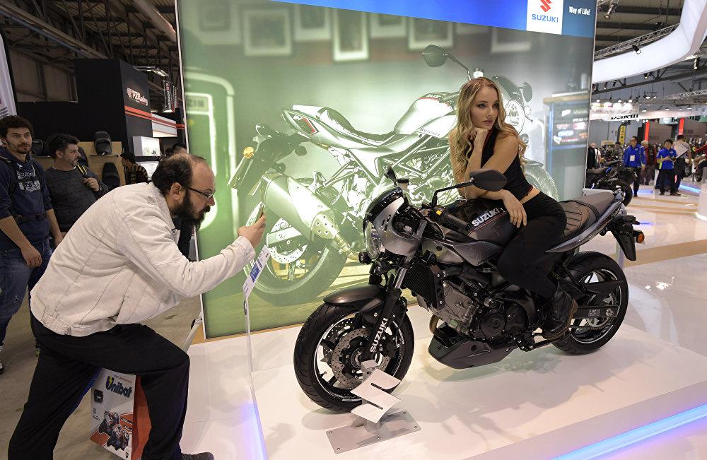 Мужчина фотографирует модель, представляющую новый Suzuki SV650X ABS в ходе миланского мотосалона