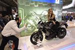 Мужчина фотографирует модель, представляющую новый Suzuki SV650X ABS