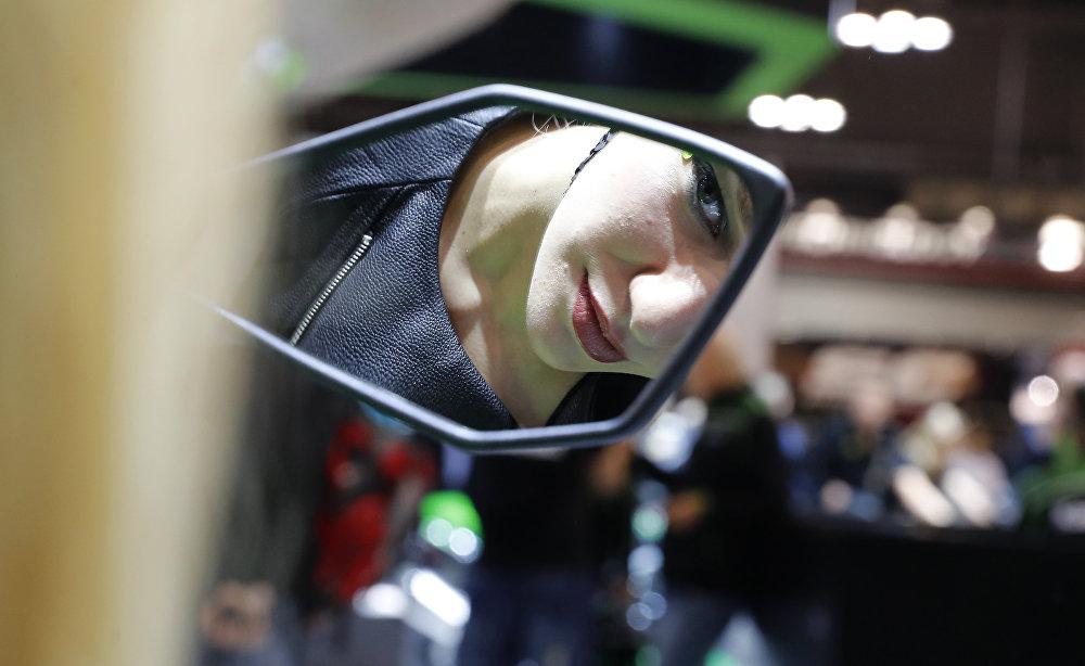 Юбилейный 75-й Миланский мотосалон продлится по 12 ноября. На фото - модель улыбается в отражении мотоциклетного зеркала