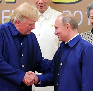 Президент РФ Владимир Путин и президент США Дональд Трамп (слева) на церемонии совместного фотографирования