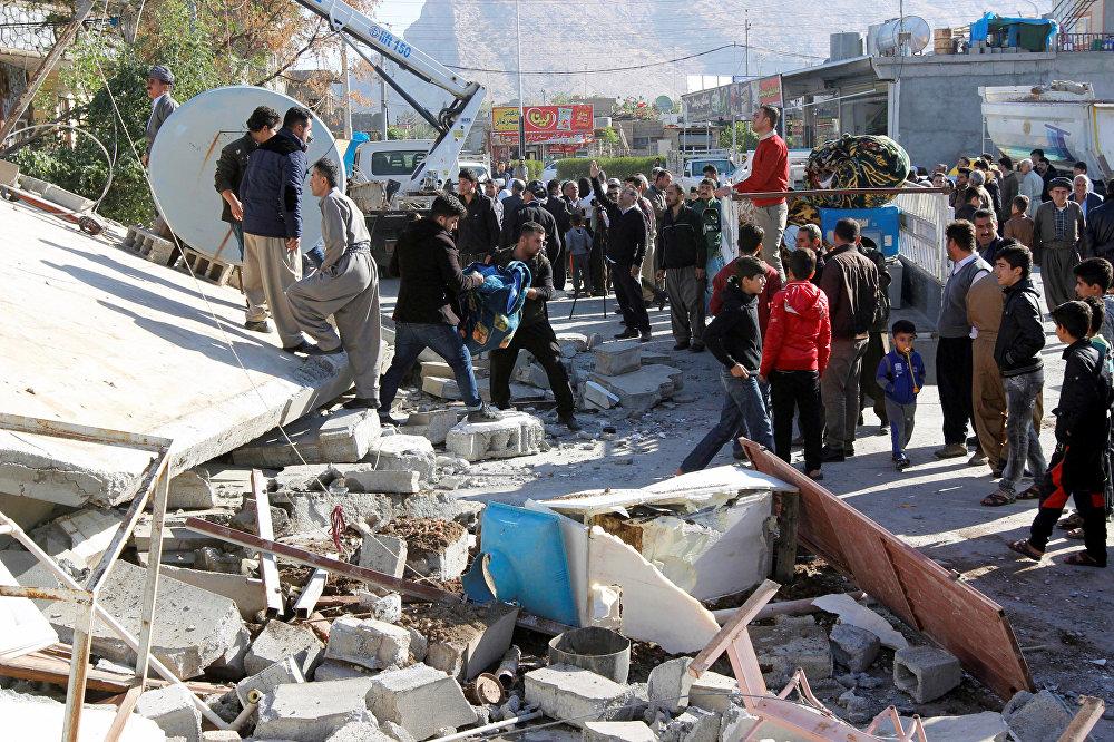 Сотни людей на улицах города Дарбандихан в Ираке помогают спасателям разбирать завалы