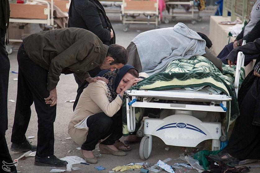 Женщина плачет у тела своего погибшего родственника в городе Сарпол-е Захаб в Иране