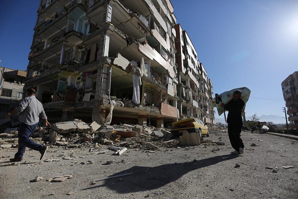 Жители города Сарпол-е Захаб в Иране на фоне города, превращенного землетрясением в руины