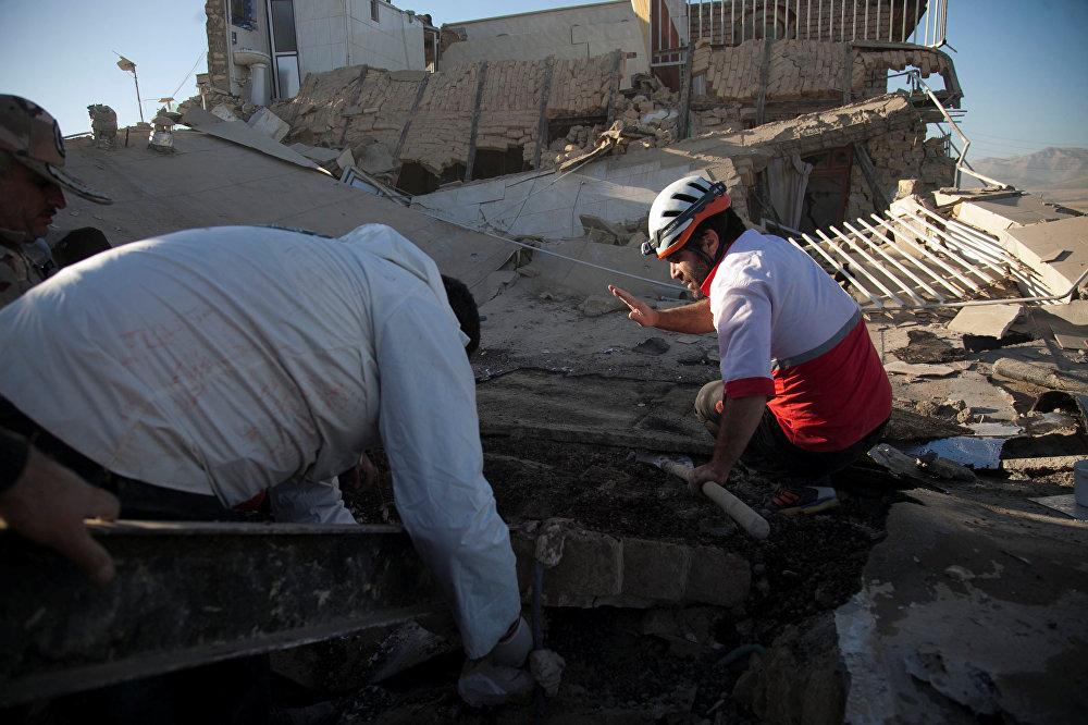 Очаг землетрясения залегал на глубине 10 километров и находился в 204 километрах от Багдада и в 104 километрах от города Керманшах. На фото - спасатели разбирают завалы в городе Сарпол-е Захаб в Иране