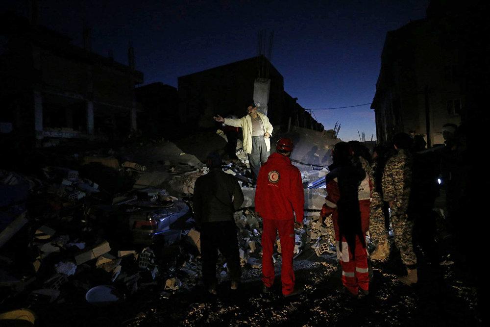 Представители спасательных служб проводят операцию по поиску выживших в городе Сарпол-е Захаб в Иране