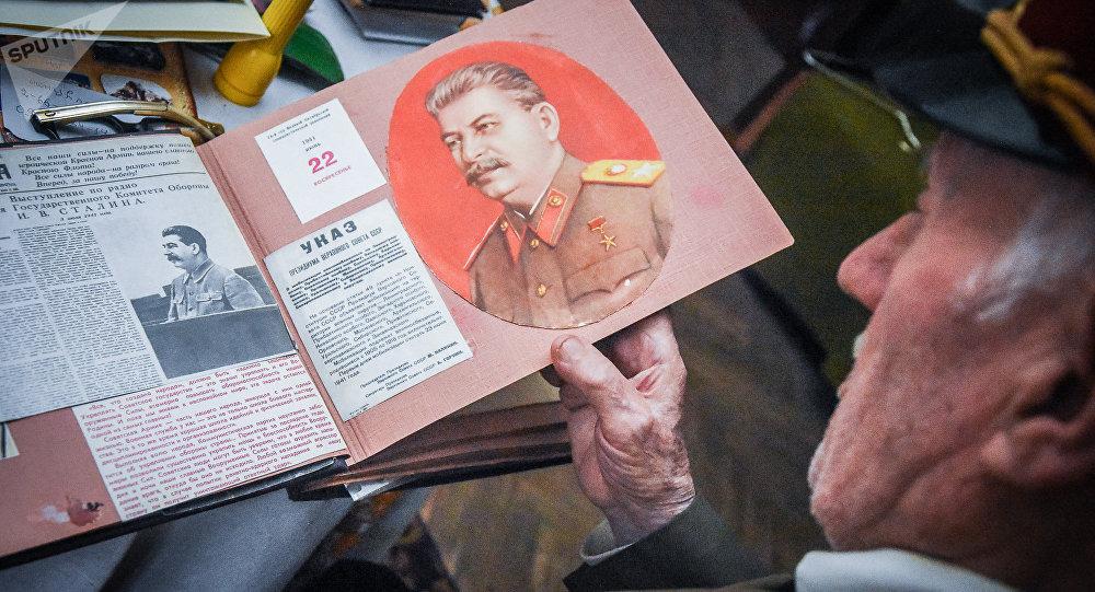 Николоз Чарашвили держит в руках альбом с изображением Сталина