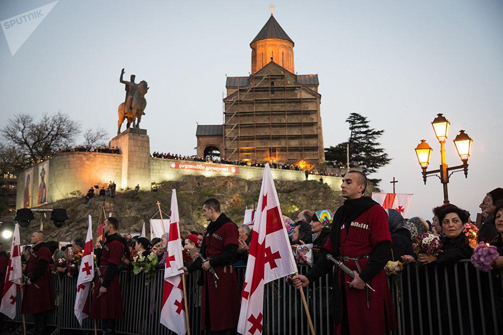 Каждый год вот уже в течение почти 800 лет грузинский народ чтит память 100 тысяч мучеников, отдавших жизни за свою веру. На Метехском мосту в историческом центре Тбилиси в этот день собираются тысячи верующих - а множество туристов, которые в обычное время также заполняют этот район столицы Грузии, снимают происходящее на камеры
