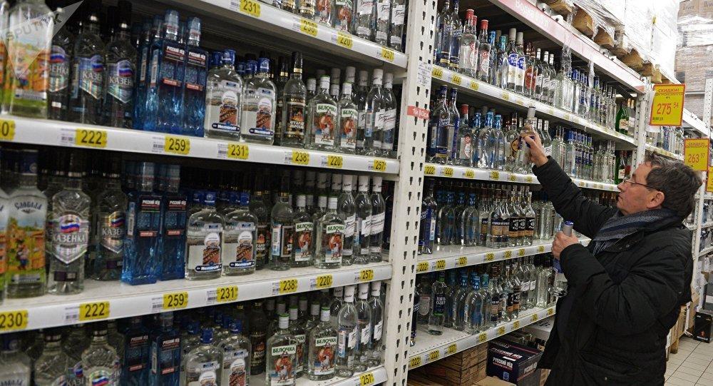 Посетитель в одном из магазинов в Москве выбирает алкогольный напиток