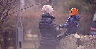 Мама с ребенком зимой в одном из парков грузинской столицы