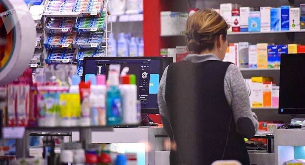 Женщина в аптеке покупает лекарства