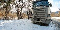 Грузовые трейлеры на обочине ожидают открытия дороги после снегопада
