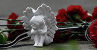 Цветы и фигурка ангела в память о погибших