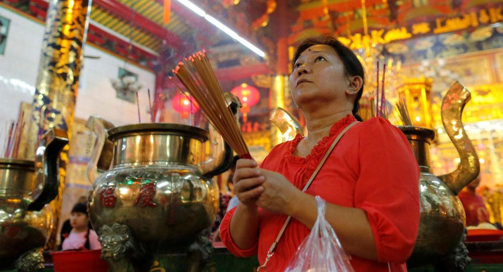 Женщина молится в храме во время китайского Нового Года в Янгоне, Мьянма