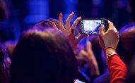 Человек снимает на смартфон концерт