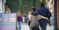 Влюбленные прогуливаются по одной из улиц в центре Тбилиси