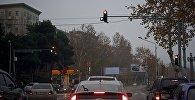 Машины на перекрестке в пасмурную погоду в Тбилиси
