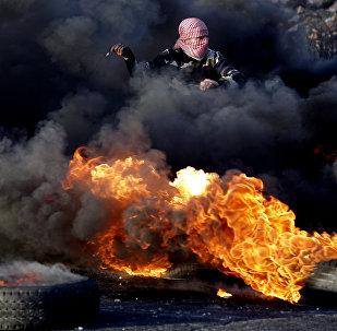 Участники акций протеста в Палестине строят баррикады в Секторе Газа и жгут покрышки. Из клубов дыма, оставаясь невидимыми, они забрасывают камнями израильских полицейских