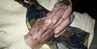 Пожилая женщина вяжет спицами