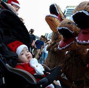 Аниматоры в костюмах тираннозавров играют с маленькими детьми в костюмчиках Санта-Клаусов в ходе предрождественской акции в торговом районе Бангкока, Таиланд