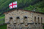Сванская башня в Местиа с грузинским флагом